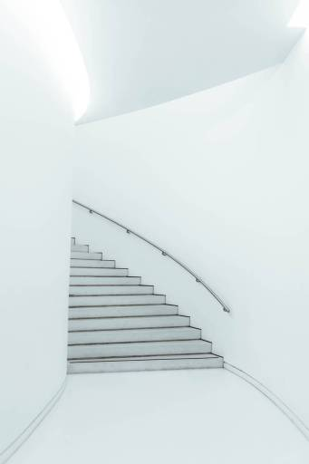 White curving staircase disappears behind a bend. Climbing the stairway of life can be simple, but is seldom easy.