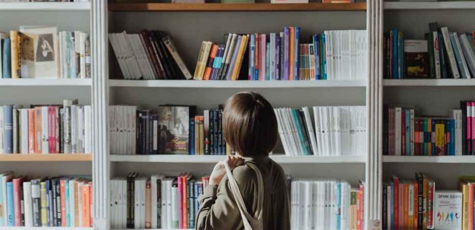 woman in beige coat standing near white wooden book shelf