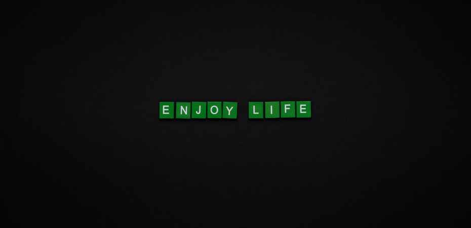 enjoy life text on green tiles with black background