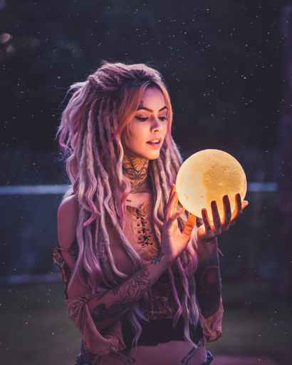 Woman with dreadlocks holds glowing orb in her hands as she contemplates her full moon ritual for manifestation.