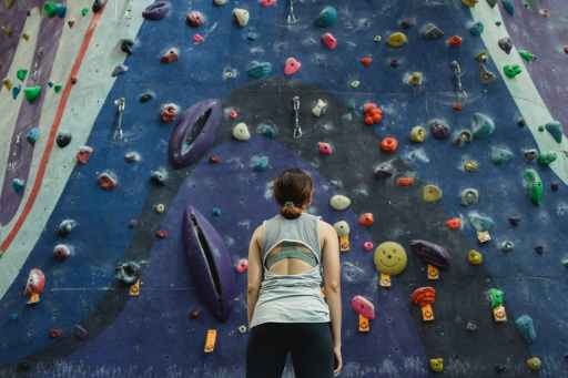 athlete standing before climbing wall evaluating her task
