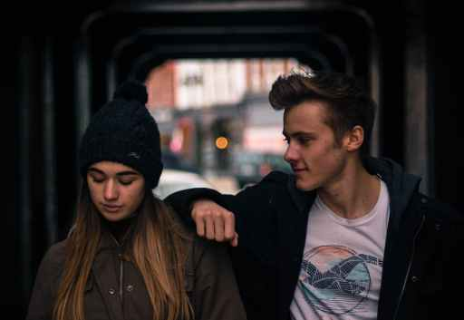 young couple in city at night unsure