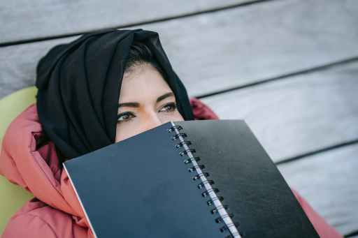pensive muslim woman with notepad in park