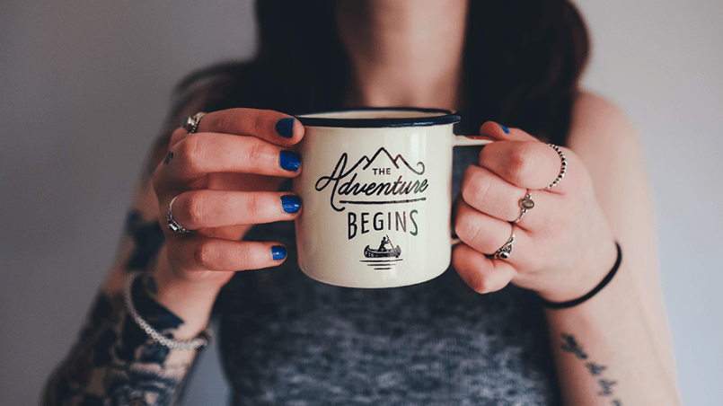 Alternative woman holding 'adventure begins' mug