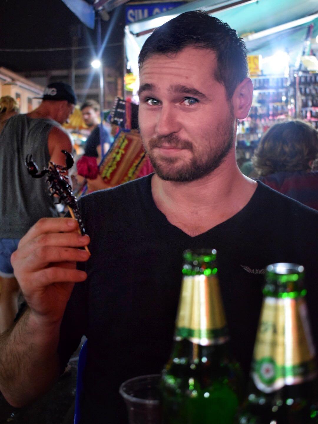 Tourist eating scorpions on Khao San Road in Bangkok, Thailand