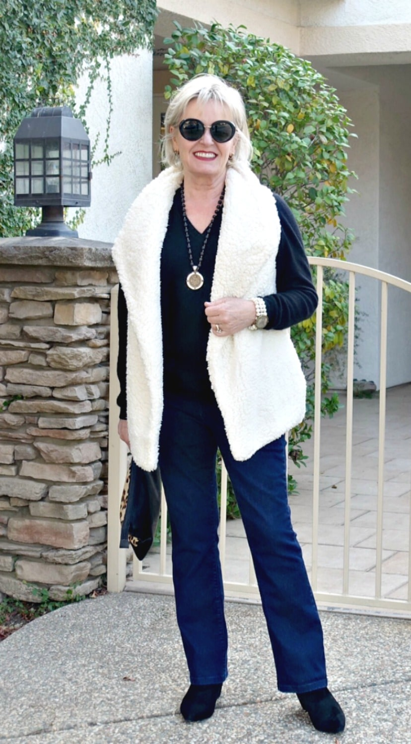 Jennifer Connolly of A well styled life wearing boot cut jeans and fleece vest with black pointed toe booties