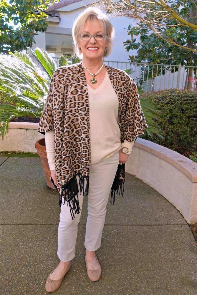 Jennifer Connolly of A Well Styled Life wearing leopard ruana, ivory sweater from Everlane with nude flats and jeans