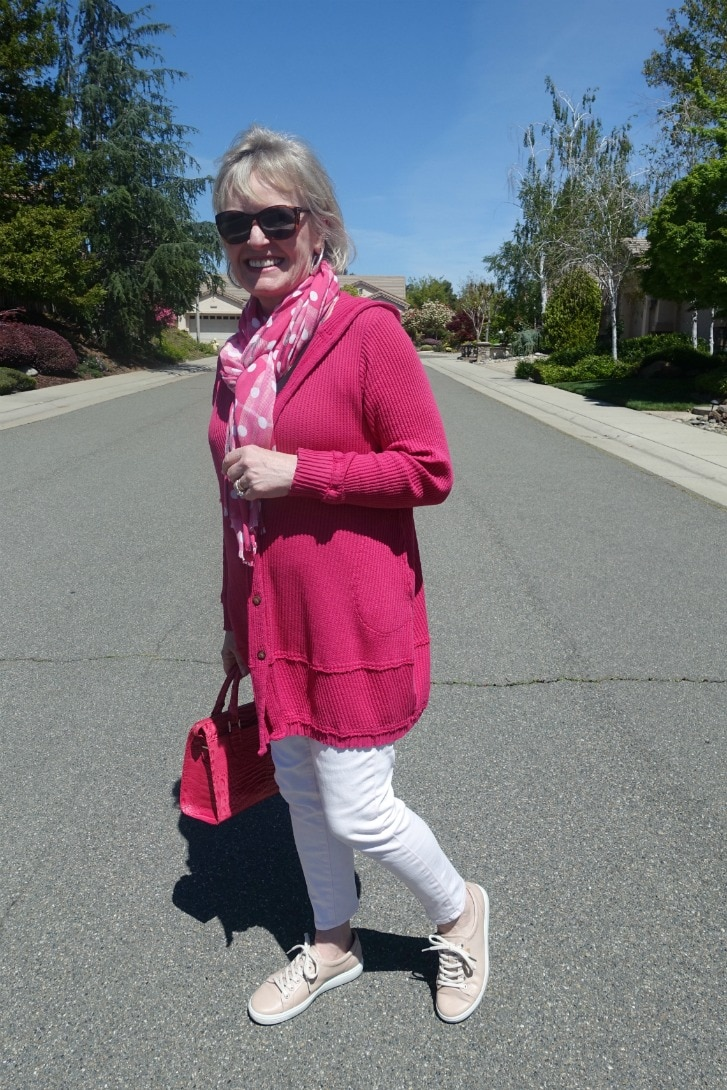 Jennifer Connolly of A Well Styled Life wear pink hoodie, pink jeans, pink handbag, and polka dot scarf