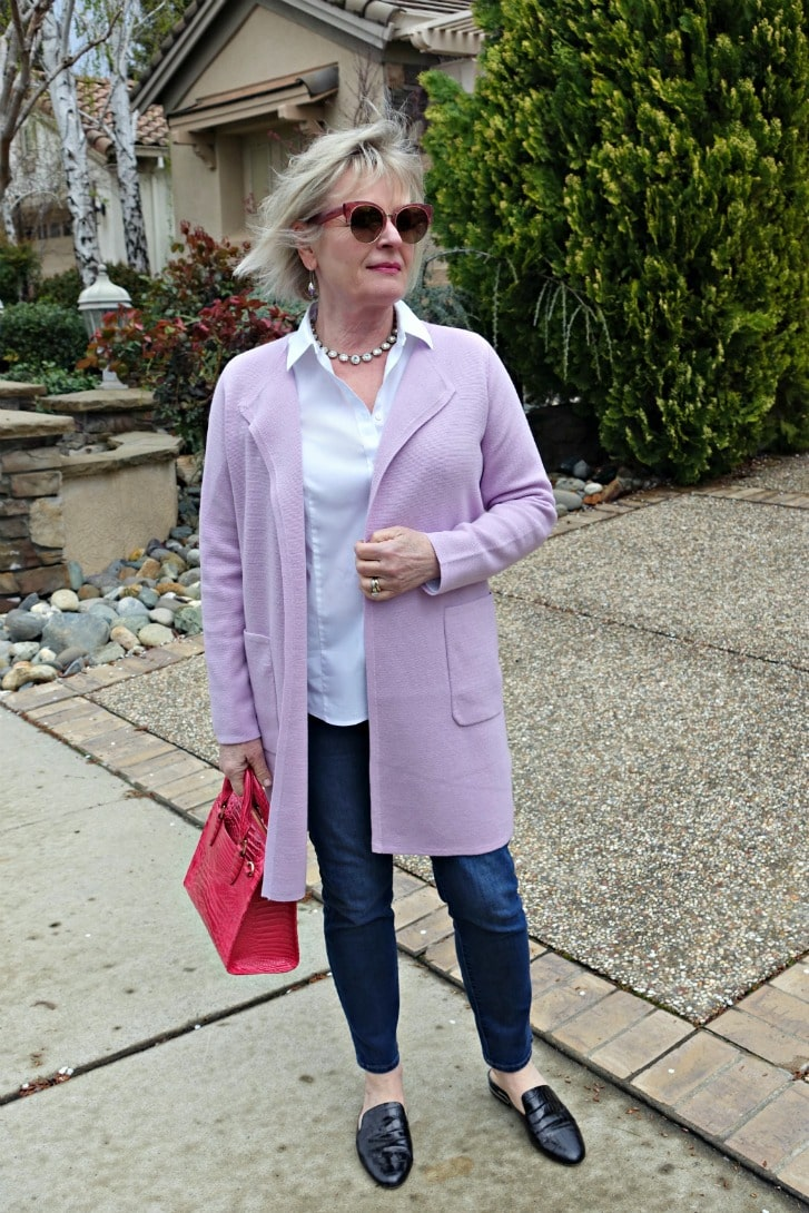 casual outfit with sweater blazer over blue jeans, white shirt and pink handbag