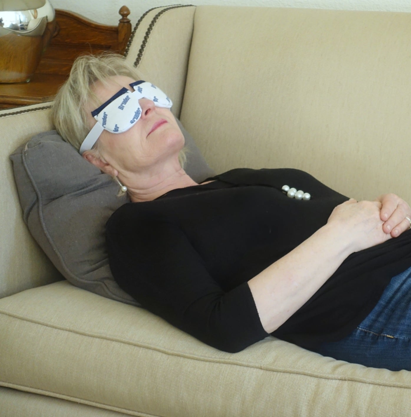 Jennifer of A Well Styled Life laying on the couch using Bruder Eye Compress