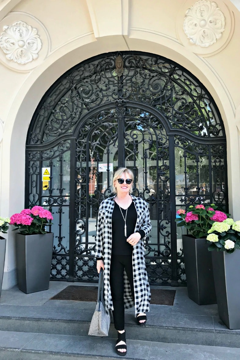 Jennifer Connolly of A Well Styled Life wearing black andc white checked duster over colum n of black