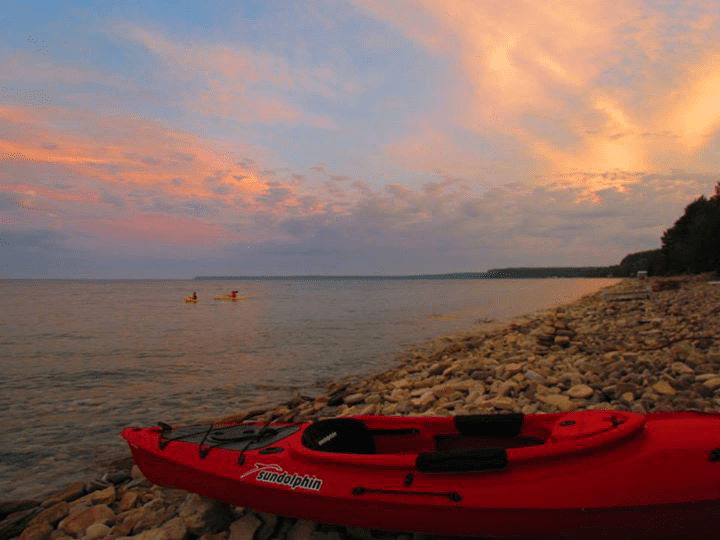 Sunset through clouds with kayak on the beach