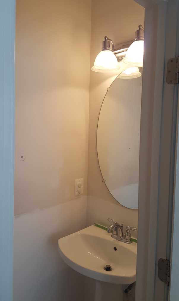 Builder Grade Powder Room Oval Mirror And Sink