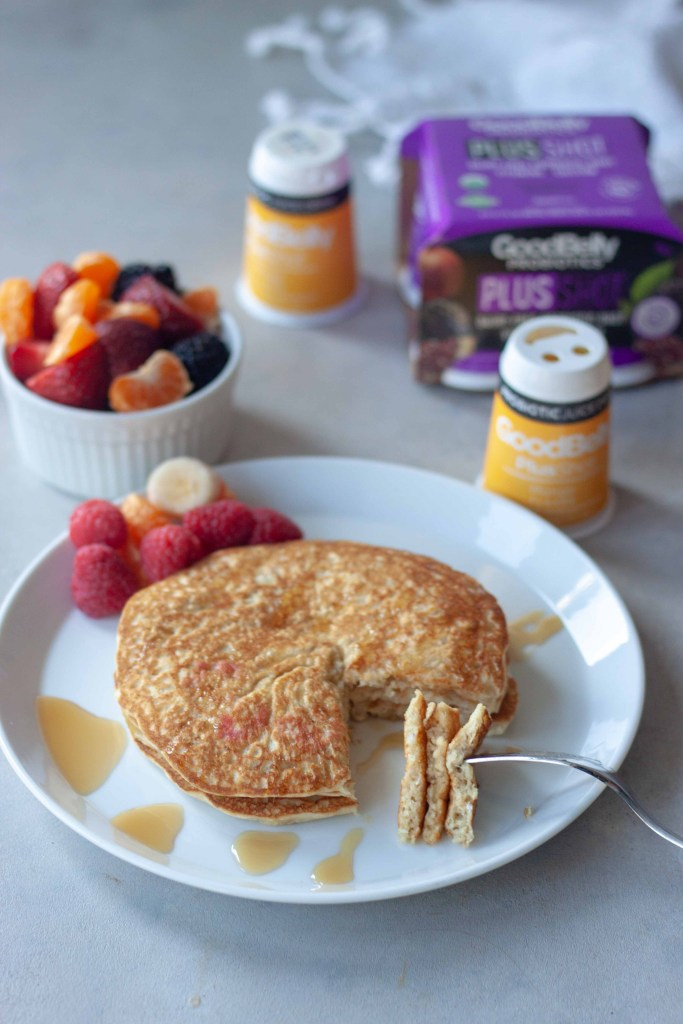 Inside of Oatmeal Pancakes topped with syrup, side of fruit and GoodBelly Probiotics.