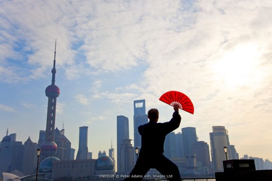 Practising Tai Chi with fan, and Pudong skyline, early morning, Shanghai, China