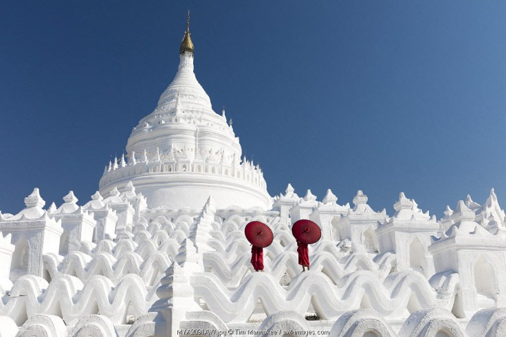 Two young Buddhist monks stand on the white walls of Hsinbyume Pagoda holding red umbrellas, Mingun, Mandalay, Myanmar