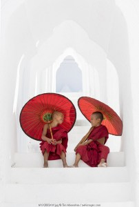 Two young Buddhist monks holding red umbrellas have fun in Hsinbyume Pagoda, Mingun, Mandalay, Myanmar