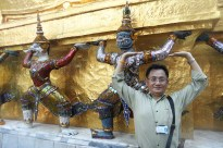 Sarunsiri poses in front of statues in the Grand Palace during a tour.