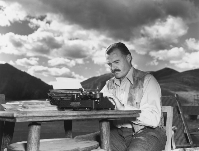 7th October 1939:  EXCLUSIVE American writer Ernest Hemingway (1899 - 1961) works at his typewriter while sitting outdoors, Idaho. Hemingway disapproved of this photograph saying, 'I don't work like this.'  (Photo by Lloyd Arnold/Hulton Archive/Getty Images)