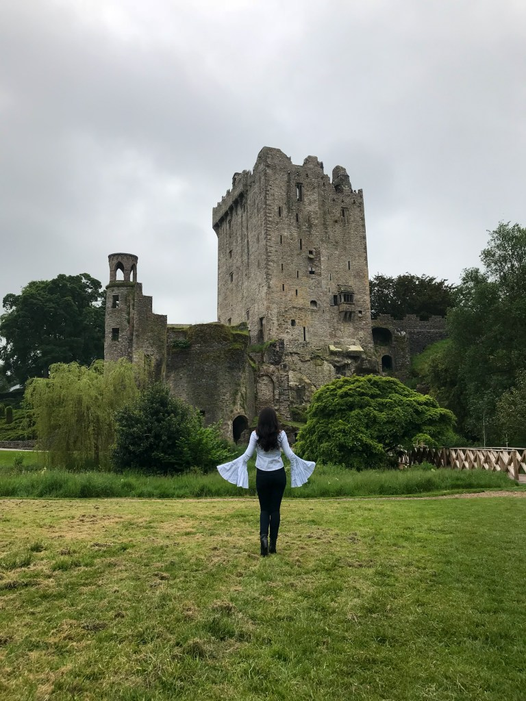 Woman standing in front of Blarney Castle in Ireland