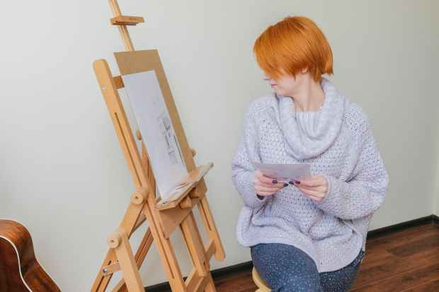 serious lady looking at sketch during painting in workshop