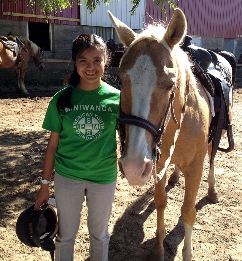 Camp Miniwanca Junior smiles next to her horse-crop