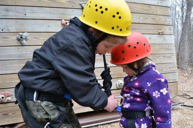 Brother helps sister prepare to climb tower at Camp Merrowvista