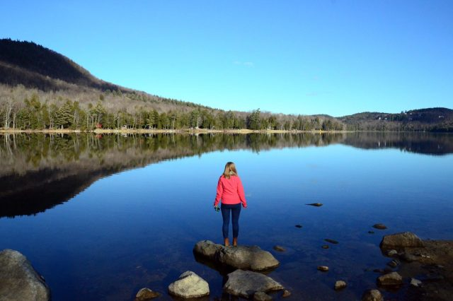 Woman reflects on rock at Camp Merrowvista waterfront