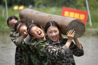 CHENGDU, CHINA - JUNE 14: (CHINA OUT) Prospective flight attendants of Chengdu East Star Airlines College take military training on June 14, 2016 in Chengdu, Sichuan Province of China. 20 prospective flight attendants from Chengdu East Star Airlines College attended a military training including creeping in water, raising logs, combat and wrestling to prepare for dealing with emergency situations on aircraft. (Photo by VCG/VCG via Getty Images)