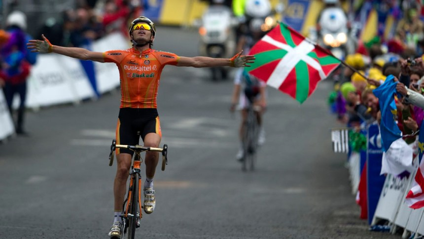 A fan waves a Basque flag as Spain's Samuel Sanchez celebrates as he wins the 211 km and twelfth stage of the 2011 Tour de France cycling race run between Cugnaux and the 2.500 metres ski resort of Luz-Ardiden, southwestern France, on July 14 , 2011. AFP PHOTO / PASCAL PAVANI (Photo credit should read PASCAL PAVANI/AFP/Getty Images)
