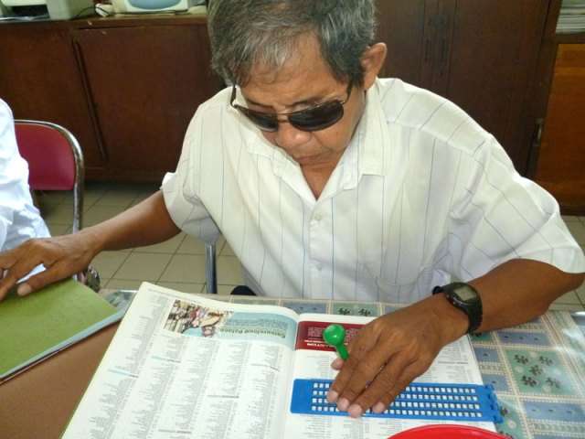 Pak Madoeri, pengajar senior, sedang menulis Braille. Selain mengajar, Pak Madoeri juga menjadi juru pijat profesional yang dapat dipanggil sewaktu-waktu.