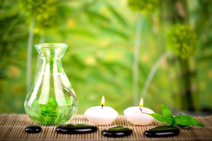 Ölflasche mit Steinen und Kerzen