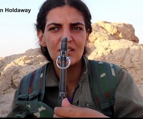 مقاتلة إيزيدية ويلاحظ انها تضع حلق إذن في رشاشتها
