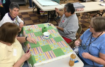 Hand tying quilts.