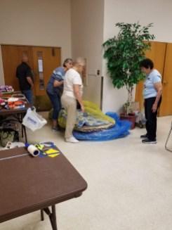 Linda, Carol, and Gloria opening big bags of quilts.