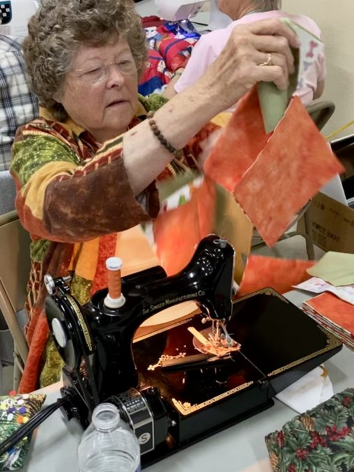 Darlene M caught in action, piecing a top on her treasured Centennial Singer Featherweight.