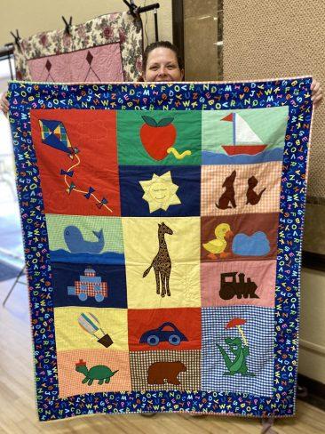 Kelli Nemec peeks over the cutest appliqué quilt that she won fair and square!