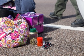 While he searches a car as part of a traffic stop, a reserve deputy for Navajo County Sheriff lays out the contents of the trunk which includes several containers of marijuana. (Photo by Emily L. Mahoney/Arizona Center for Investigative Reporting)