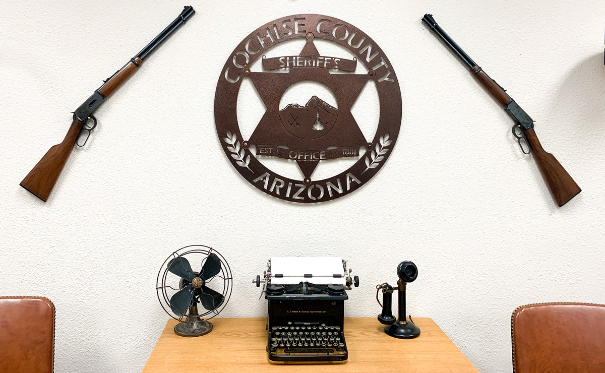 Rifles border the Cochise County Sheriff's seal on a wall at the department headquarters in Southern Arizona. Photo by Terry Greene Sterling/AZCIR