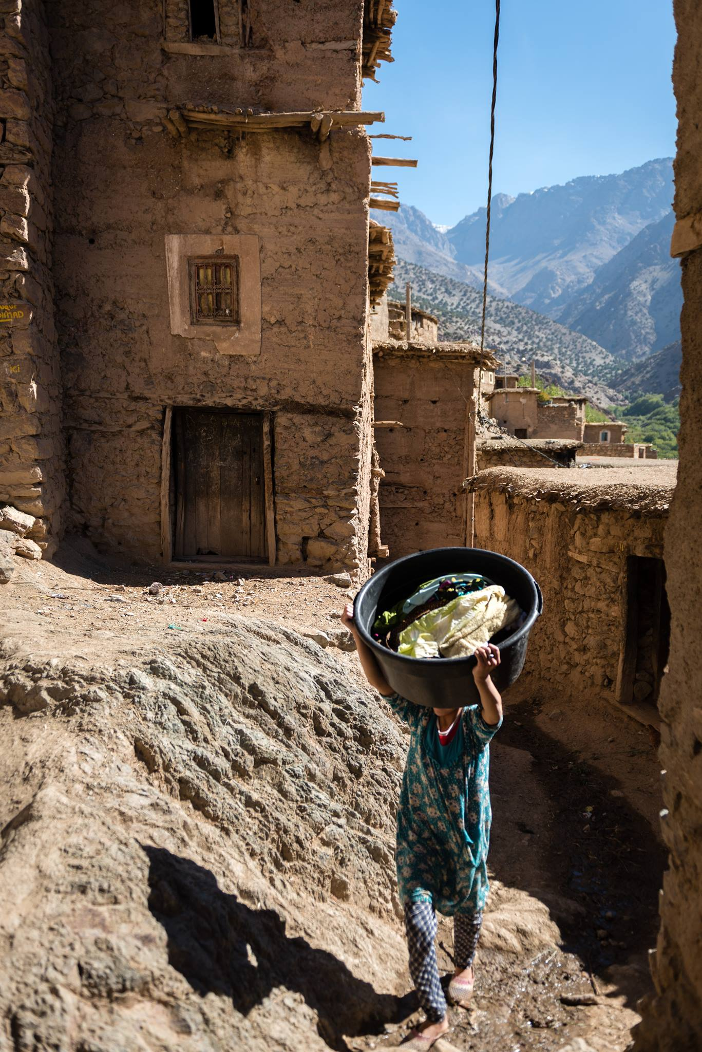 Woman carrying laundry on her head, Hight Atals mountins