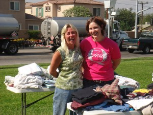 Two ladies organize a yard sale with a smile on their faces