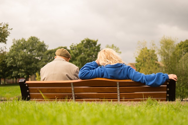 Two old people sitting on a bench