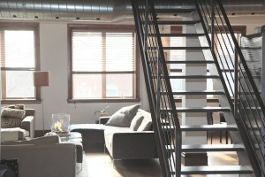 a living room in an appartment with a flight of stairs on the right