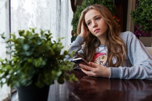 A teenage girl sitting next to a window and holding her mobile in her hand.