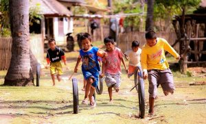 A few kids running with sticks and rolling bicycle tires.