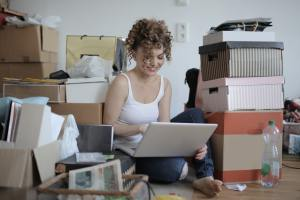 A woman sitting between boxes working on a laptop.