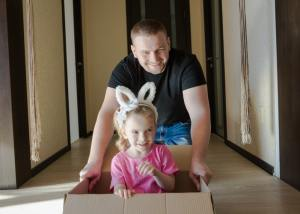 Dad pushing a cute little girl in a cardboard moving box.
