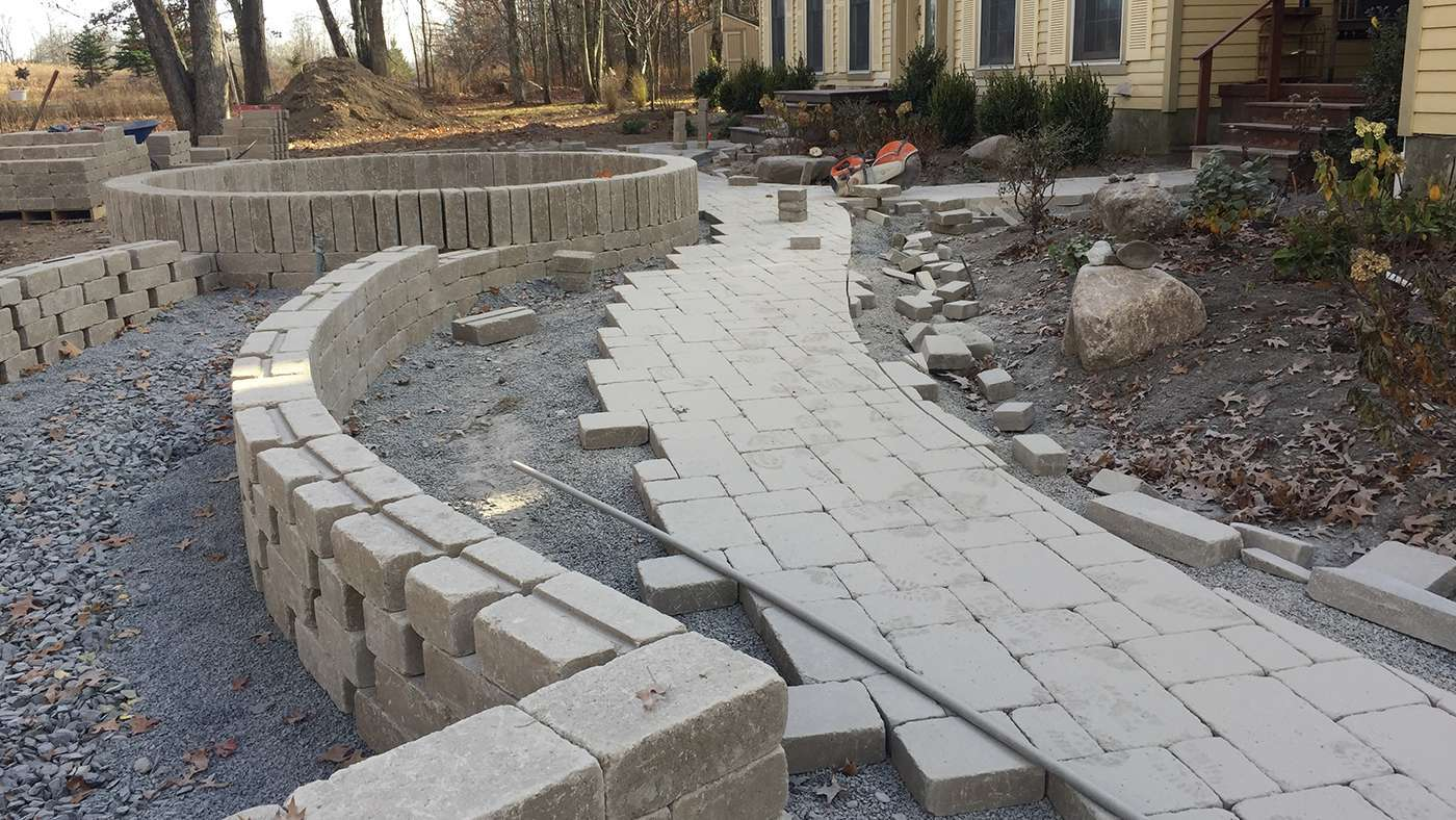 Unilock brussels pavers are being installed along with flower beds, in New Paltz NY