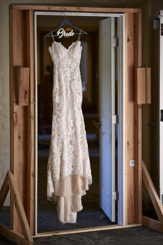 Wedding dress hanging in under construction door.