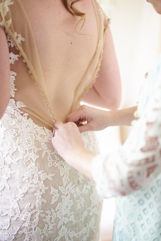Buttoning the bride's wedding dress.